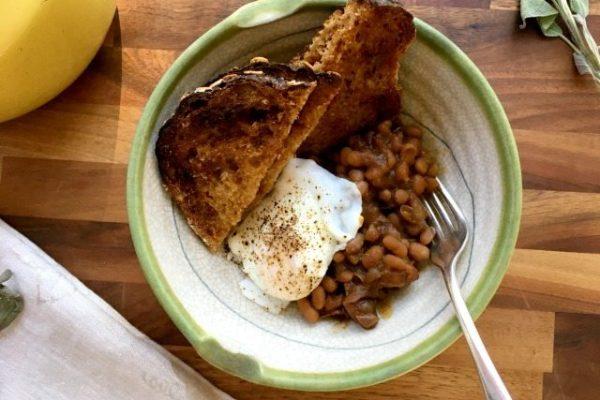 feves au lard avec pain et oeuf dans une assiette